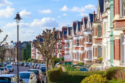 Row of typical English terraced houses in West Hampstead, London with a To Let sign outside