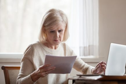 frustrated middle aged senior woman worried inspecting paper letter document