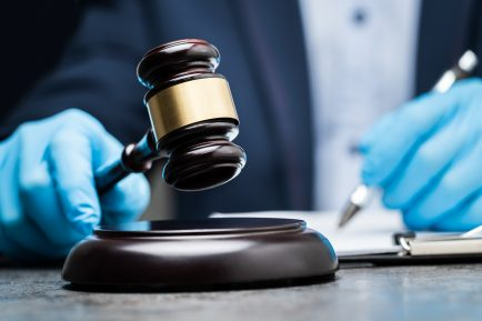 Judge In Gloves To Protect From Coronavirus Writing On Paper