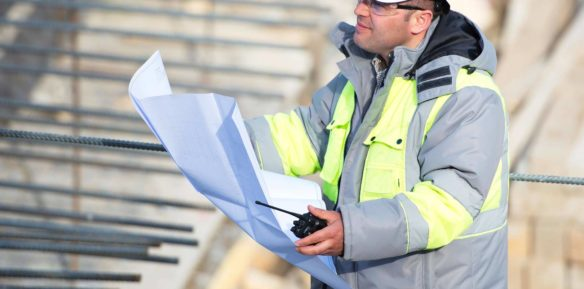An engineer working on site with plans
