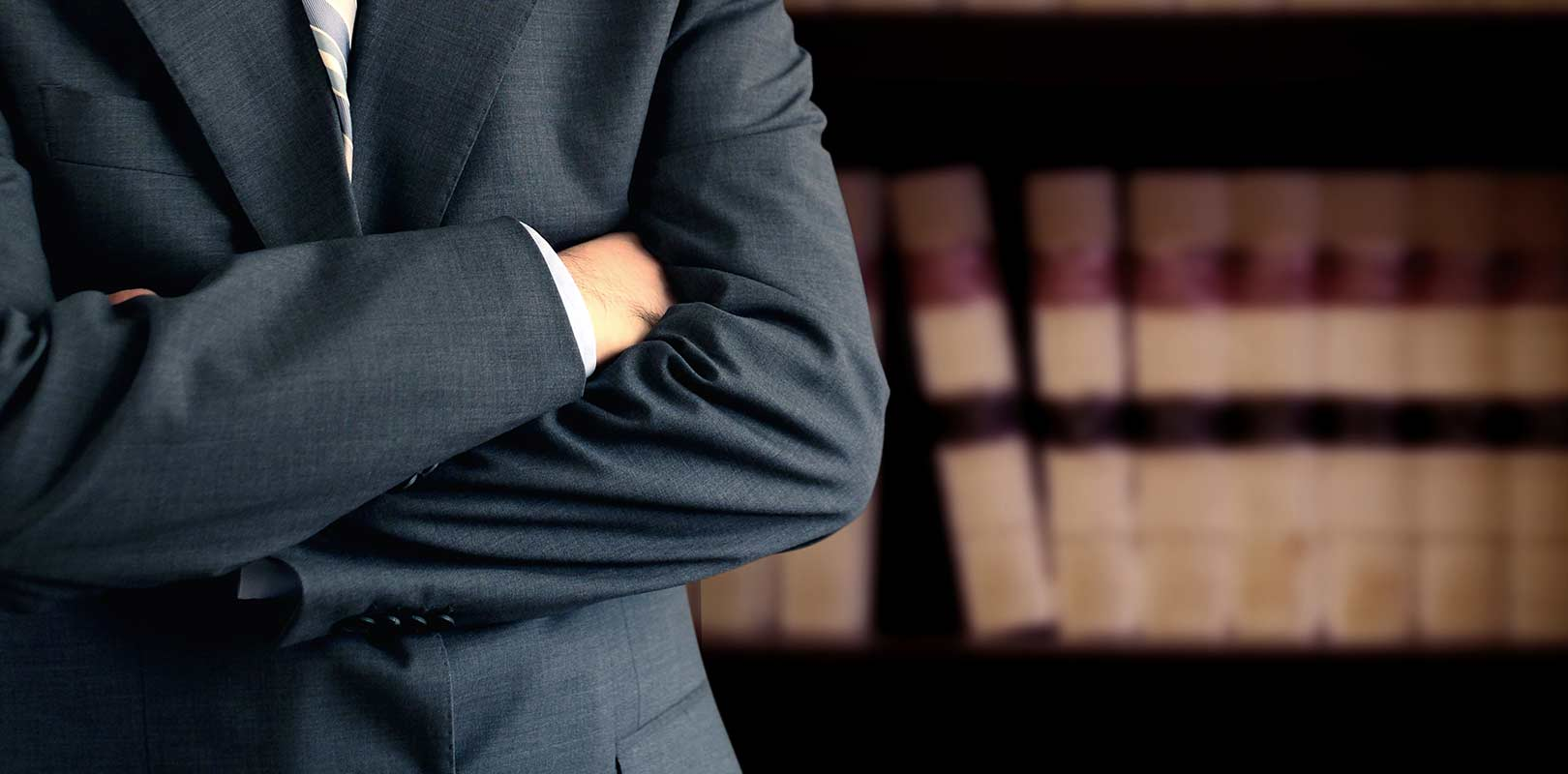 Solicitor with arms folded and law books behind on a shelf