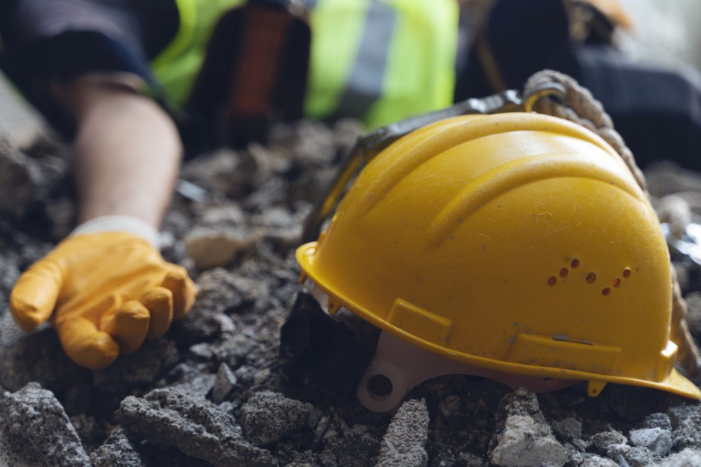 construction worker has an accident while working on new house. construction worker lies on the floor at the work site. work accident